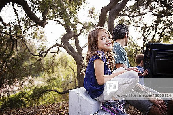 Glückliches Mädchen schaut weg  während es mit seiner Familie im Wald sitzt
