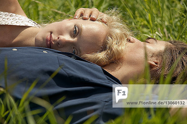 Portrait of woman leaning on man's chest while lying in grass field