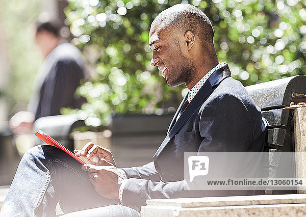 Businessman using tablet computer while sitting at city street