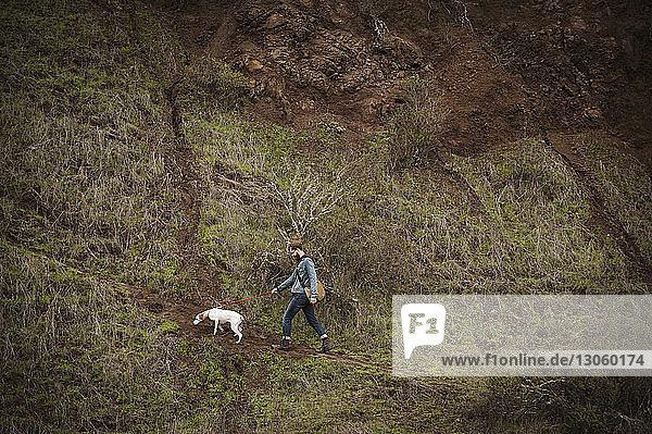 Mann mit Hund beim Waldspaziergang