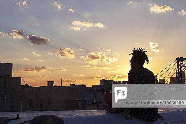 Silhouette eines Mannes  der auf einer Stützmauer gegen die Stadt sitzt