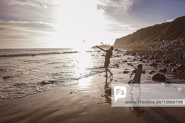Vater und Sohn werfen bei Sonnenuntergang Steine ins Meer