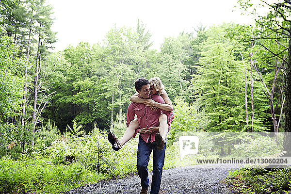 Man piggybacking woman while walking on gravel road by field