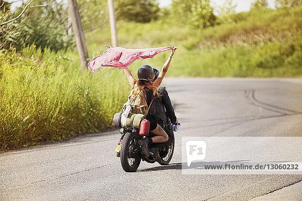 Frau hält Schal in der Luft  während sie mit dem Mann auf dem Motorrad sitzt
