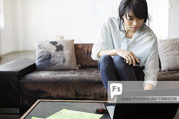 Businesswoman using laptop while sitting on sofa