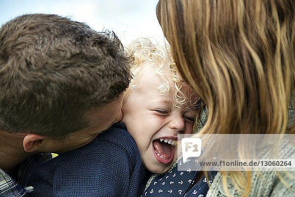 Nahaufnahme von Eltern  die ihren glücklichen Sohn umarmen