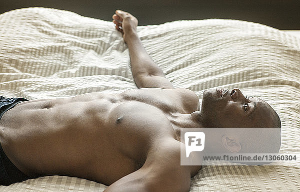 High angle view of man relaxing on bed at home