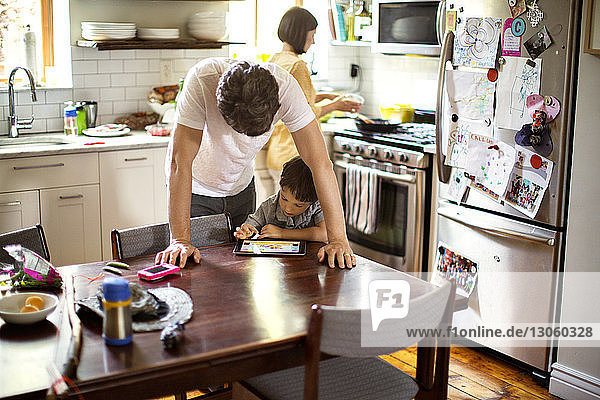 Father and son using tablet computer at dining table in kitchen