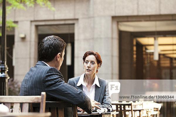 Geschäftsmann und Geschäftsfrau diskutieren  während sie im Straßencafé sitzen
