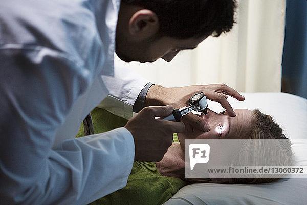 Arzt untersucht das Auge des Patienten im Krankenhaus mit dem Otoskop
