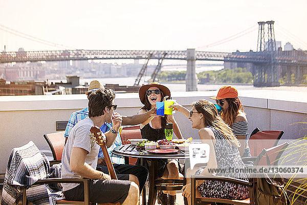 Freunde genießen Frühstücksparty auf der Gebäudeterrasse gegen die Williamsburg Bridge