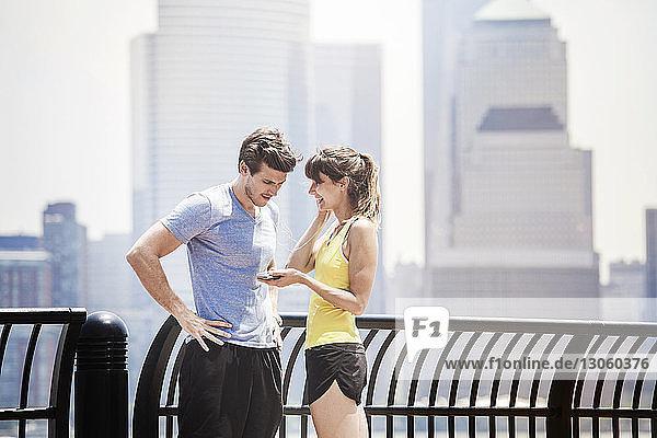 Paar hört Musik auf einem Smartphone  während es an der Reling steht