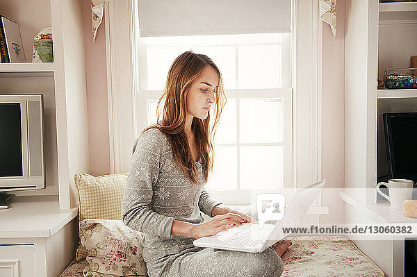 Young woman using laptop while sitting on window seat at home