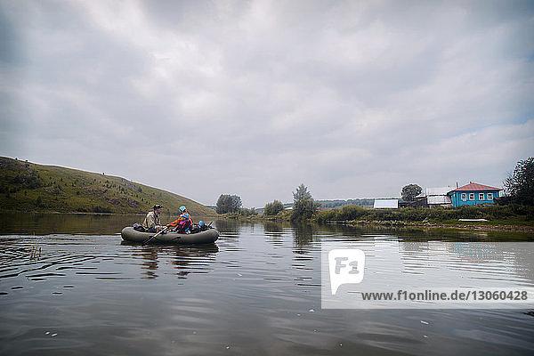 Freunde reisen auf einem Floß am Fluss gegen bewölkten Himmel