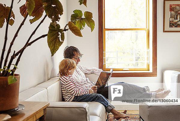 Vater und Sohn lesen Buch  während sie zu Hause auf dem Sofa sitzen