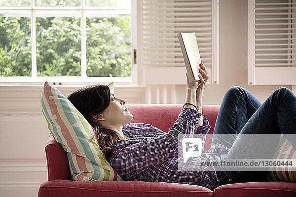 Frau liest Buch im Liegen auf dem Sofa