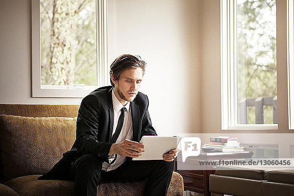 Man using tablet computer while sitting on sofa at home