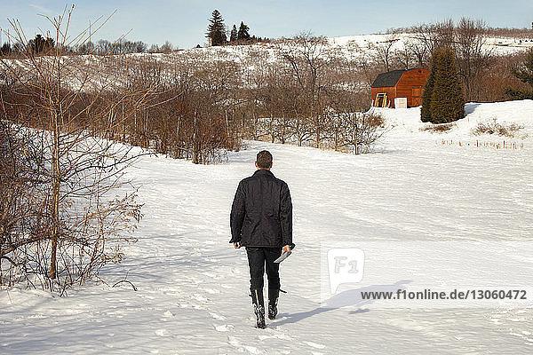 Rückansicht eines Mannes  der auf einem schneebedeckten Feld läuft