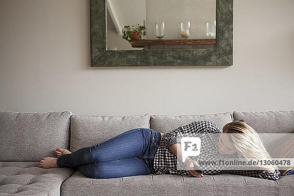 Mädchen in voller Länge benutzt ein Smartphone  während sie zu Hause auf dem Sofa liegt