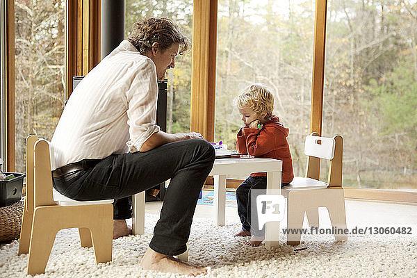 Vater und Sohn sitzen zu Hause auf Stühlen
