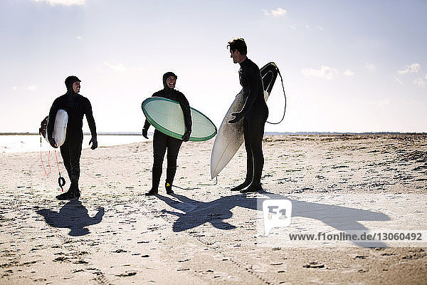 Surfers carrying surfboard while standing at beach