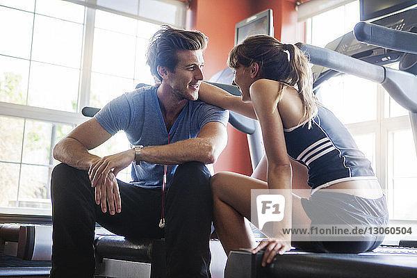 Glückliches Paar sitzt im Fitnessstudio auf dem Laufband