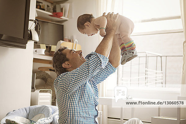 Happy father lifting baby girl at home