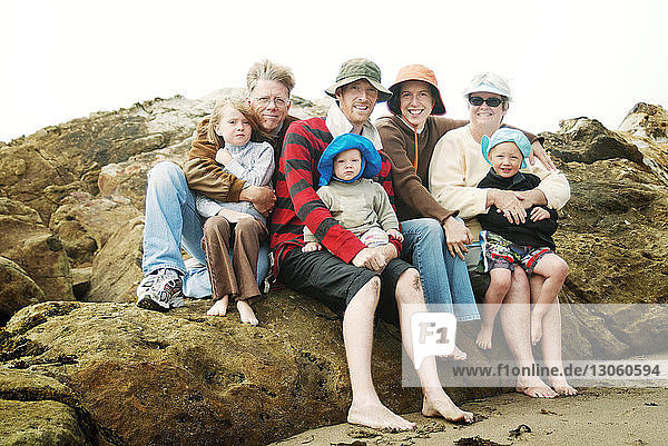 Porträt einer Familie  die auf einem Felsen gegen den Himmel sitzt