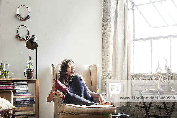 Thoughtful woman sitting on armchair at home