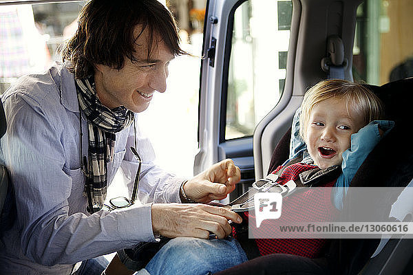 Father looking at son while fastening seat belt in car