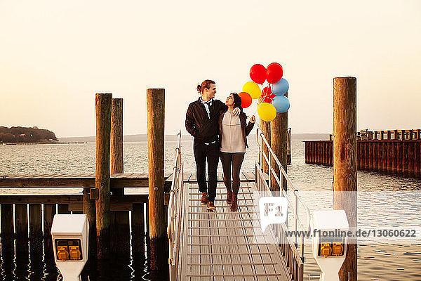 Frau hält Heliumballons  während sie mit dem Mann bei Sonnenuntergang am Pier spazieren geht