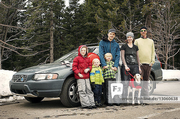 Portrait of family with dog standing by car on road