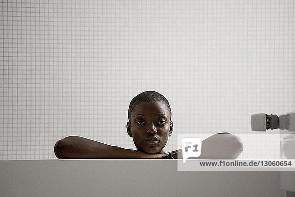 Portrait of woman sitting in bathroom