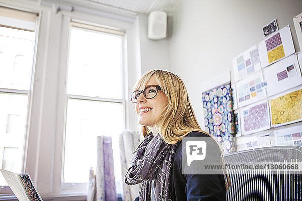 Seitenansicht einer fröhlichen Modedesignerin  die in einem Workshop sitzt