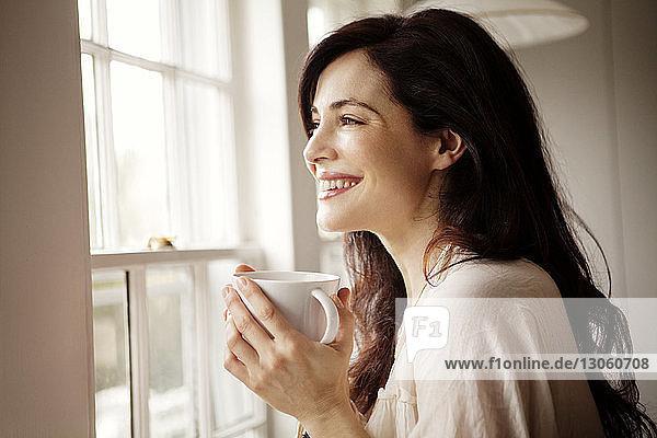 Lächelnde Frau mit Kaffeetasse  die zu Hause durch das Fenster wegschaut