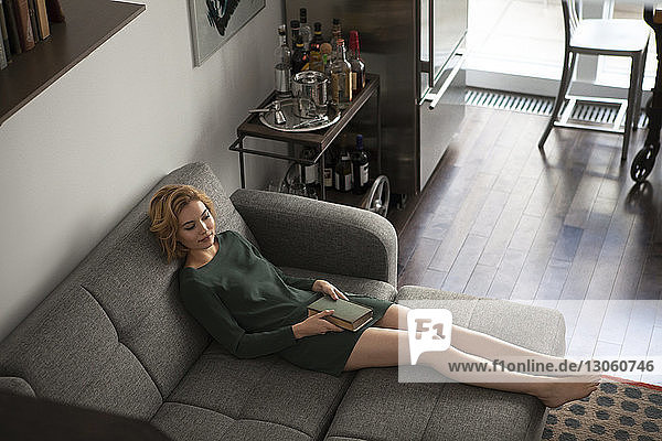 High angle view of woman with book on sofa