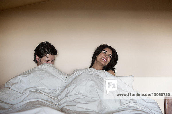 Cheerful couple relaxing under blanket on bed