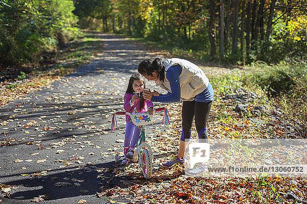 Mutter zeigt der Tochter ein Handy  während sie auf dem Feld steht