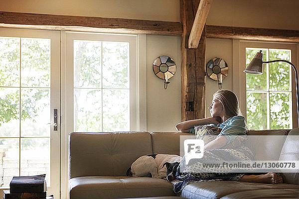 Nachdenkliche Frau schaut weg  während sie zu Hause auf dem Sofa sitzt