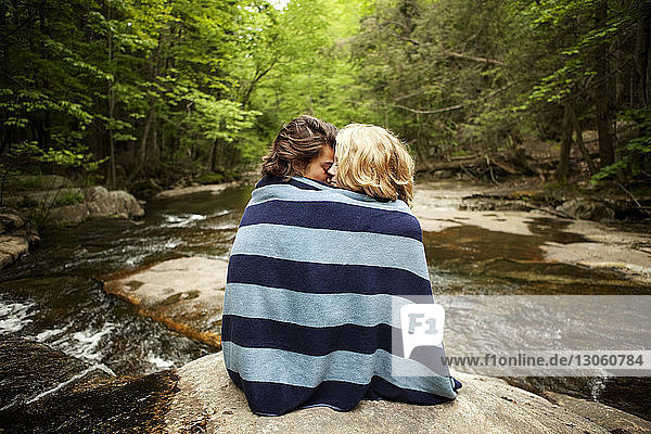 Couple wrapped in towel sitting on rocks in river