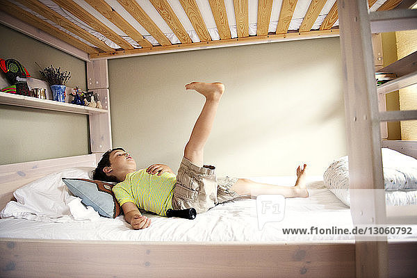 Boy with feet up relaxing on bed at home