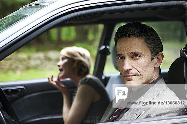 Man looking away while woman adjusting lipstick in car