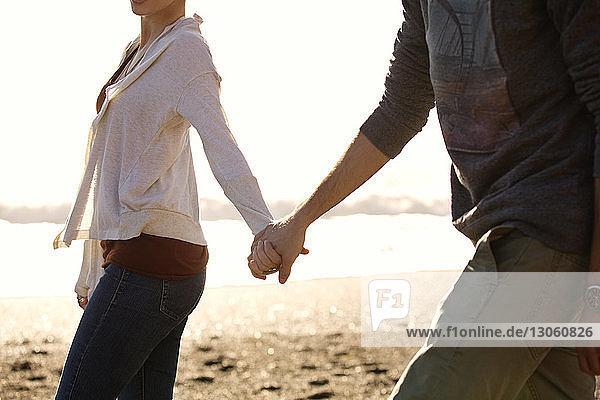 Paar hält sich beim Strandspaziergang an den Händen