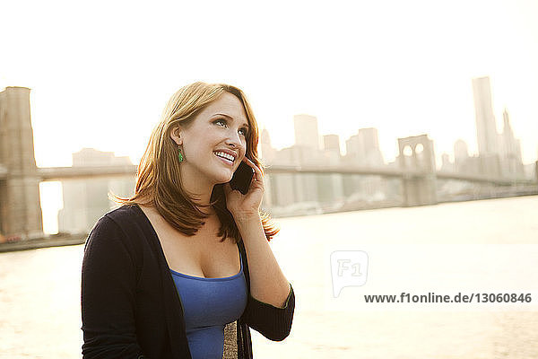 Beautiful woman talking on mobile phone against East River on sunny day