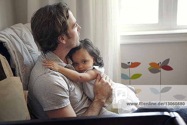 Father sitting with daughter at home