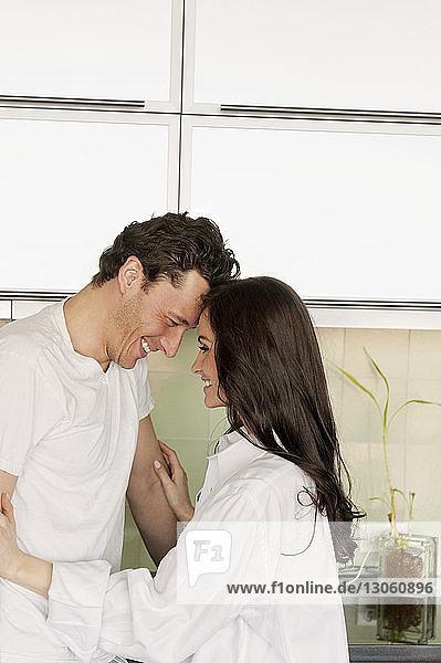 Seitenansicht des in der Küche stehenden glücklichen Paares