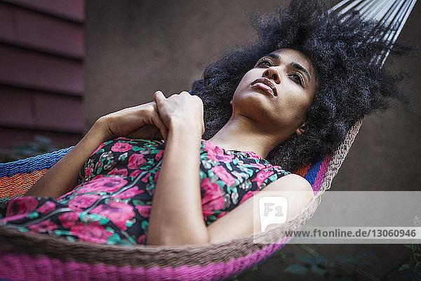 Frau schaut weg  während sie sich auf Hängematte ausruht