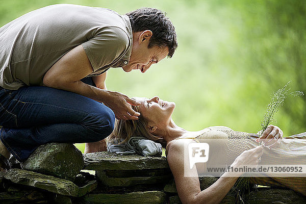 Man looking at woman lying on stone wall