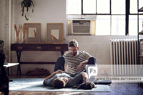 Mann betrachtet Freund  der zu Hause auf dem Boden liegt