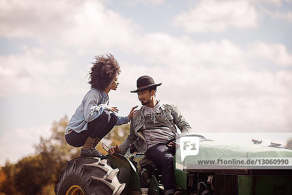 Couple on tractor against cloudy sky